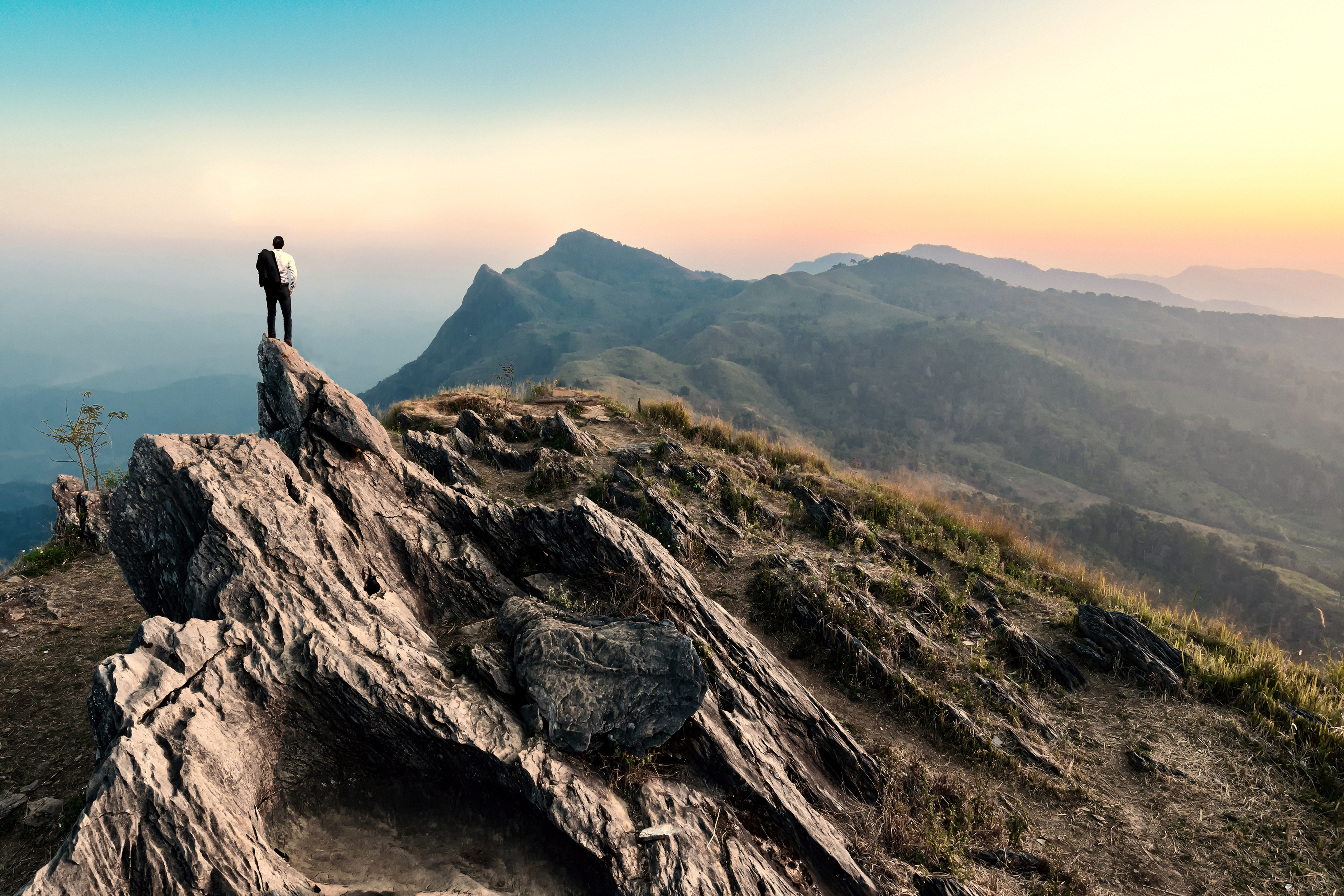 Businessman hiking on peak of mountain at sunset_XXL.jpg